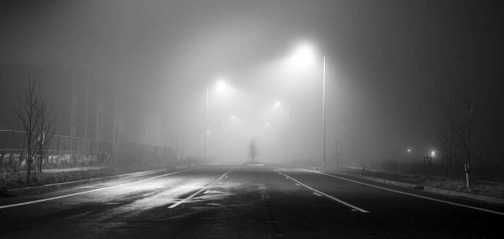 Black and white street at night with fog
